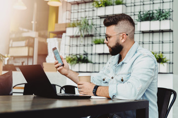 Hipster man with smartphone in his hand, sitting in cafe at lunchtime and drinking coffee. On table is laptop and notebook. Businessman in casual clothes sends text message on phone. Online education.