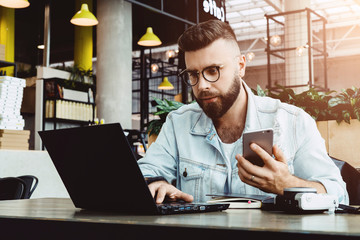 Hipster man sits in cafe, uses smartphone, works on laptop. Businessman reads an information message in computer. Freelancer works outside office, teleworking. Online marketing, education for adult.