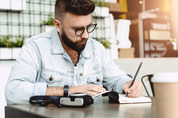 Young bearded hipster man sits in cafe at table, writes in notebook. Journalist writes information in notepad. On table cup of coffee, camera. Man is working, studying, learning. Education for adult.