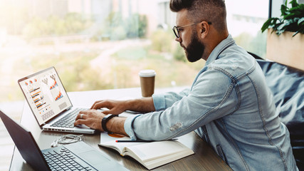 Hipster man sits in cafe, works on laptop with charts, graphs, diagrams on screen. Businessman checks information on phone, planning business. On table is notebook, paper documents. Online marketing.