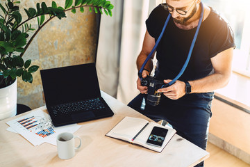 Man looks at camera screen,sitting in office at table with cup of coffee and laptop. Photographer is watching footage on camera screen. On desk notebook, smartphone.Concept of occupation and lifestyle