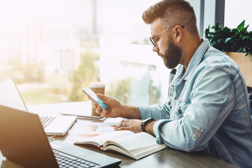 Side view. Young bearded hipster businessman working on laptop while checks information on smartphone. Man millennial reads message on phone, checks e-mail. Student is studying online. Adult education