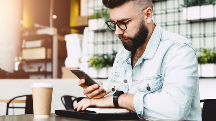 Serious hipster man reading message on smartphone while sitting in cafe at table. Guy checks mail through smartphone while relaxing in restaurant. Businessman checks information using phone. Education