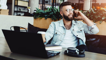 Smiling bearded businessman in glasses sitting in cafe, talking on smartphone, drinking coffee, blogger working in coffee shop, hipster man having conversation on cell phone. Online trading,education.