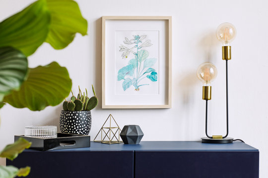 White interior of floral poster mock up with vertical wooden frame, table lamp, , cacti, gold pyramid and tropical flowers  on the white wall background. Concept with navy blue shelf.