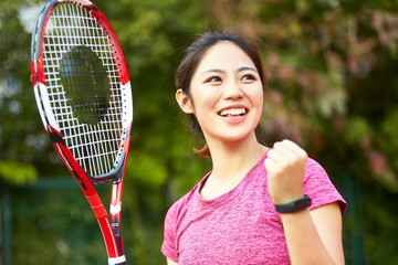 portrait of happy asian female tennis player