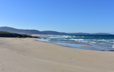 Wild beach with golden sand, rocks and blue sea with waves and white foam. Clear sky, sunny day. Galicia, Coruna Province, Spain.