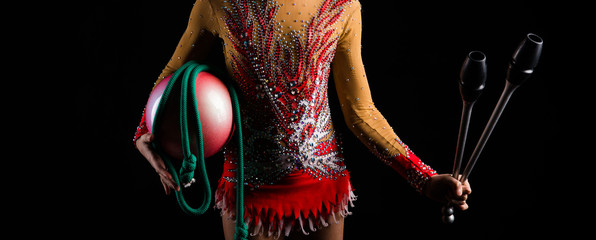 Teenager girl gymnast holding in her hands the accessories for rhythmic gymnastics
