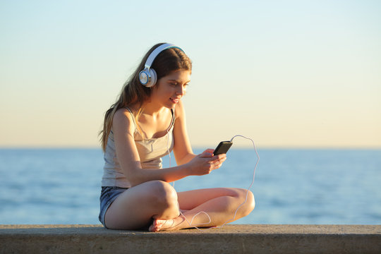 Full body of teen listening to music from smart phone