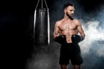 pensive sportsman in boxing gloves standing near punching bag on black with smoke