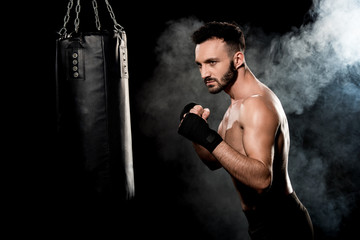 muscular athlete standing in boxing pose and looking at punching bag on black with smoke