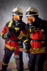 Feuerwehr Angriffstrupp mit Feuerwehraxt, Flamen spiegeln sich in der Atemschutz Maske