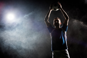 silhouette of cheerful football player holding ball above head on black with smoke