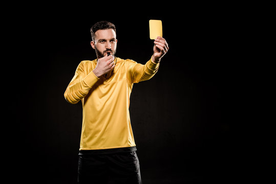 handsome referee showing yellow card and blowing whistle isolated on black
