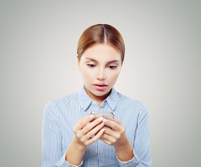 Shocked woman on cellphone. Girl texting on smartphone