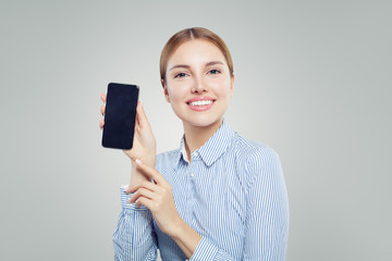 Girl showing cell phone with empty copy space. Happy woman with smartphone. Presenting your product.