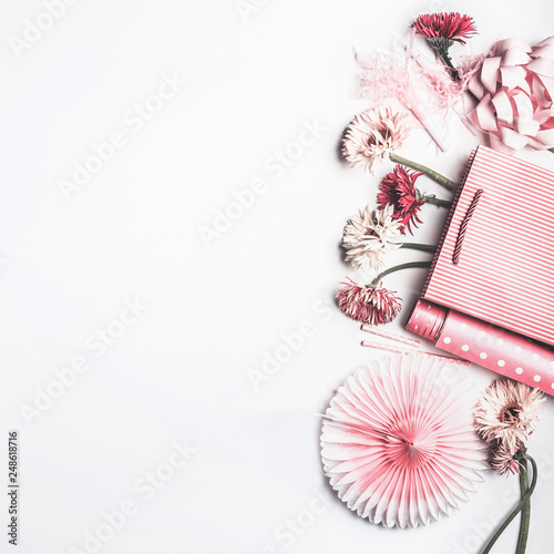 Flat lay composition of pink accessories to female holidays: Mothers day , Womens day, birthday. Paper shopping bag with flowers,paper, party fan and ribbon on white background, top view, border