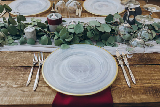in the wedding banquet area there are tables and transparent chairs, on the tables there are plates, glasses, cutlery and compositions from green branches and candles