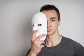 young man taking off plain white mask revealing face                Wall mural