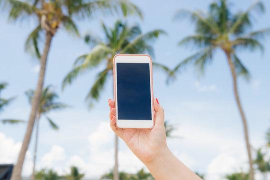 Beautiful woman's hand using smart phone at beach.