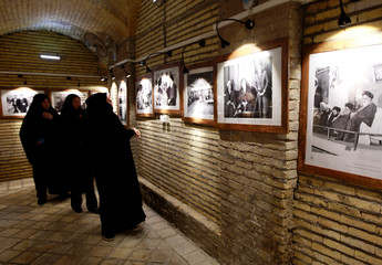 Iranian pilgrims look at the pictures of the late Iranian revolutionary leader Ayatollah Ruhollah Khomeini, at the former home of Khomeini in Najaf
