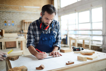 Thoughtful concentrated middle-aged bearded carpenter with ear protectors on neck standing at table and using ruler while making sketch