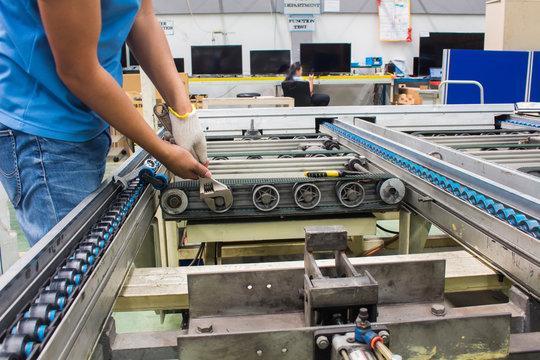 worker maintenance and repair conveyor belt in factory