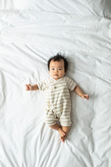 From above photo of cute Asian baby lying on bed and looking at camera.