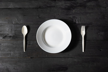 Empty white bowl, fork and spoon on black wood table, top view. Diet concept: flat lay of clean kitchen dishes on dark rustic background
