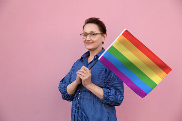 LGBT flag. Woman holding rainbow flag. Nice portrait of middle aged lady 40 50 years old holding a large flag over pink wall background on the street outdoor.