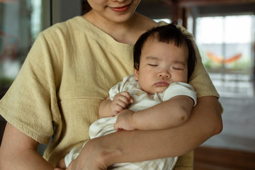 Cute Asian baby sleeping in her mother's arms.
