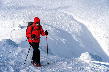 Winter sport activity. Woman hiker hiking with backpack and snowshoes snowshoeing on snow trail.