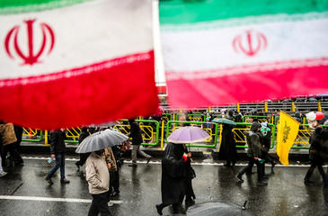 Iranian people carry umbrella during a ceremony to mark the 40th anniversary of the Islamic Revolution in Tehran