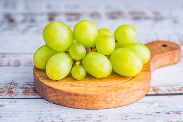 A small bunch of green grapes on a small round wooden serving board