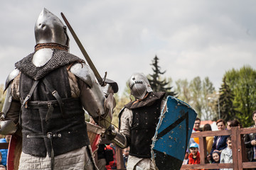 Knight tournament. The knights in the congregations are fighting in the ring. Public event in the city. Soldiers in armor of the Middle Ages.