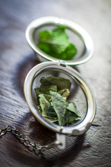 Metal tea infuser with dried leaves of green tea and fresh mint on a dark brown wooden background