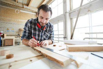 Content handsome middle-aged carpenter with stubble wearing ear protectors on neck drawing straight line with ruler while working with wooden plank