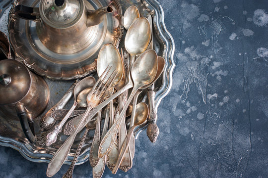 Melkhiorovye vintage dining items (tray, kettle, forks, knives, spoons,) top view, horizontal, copy space