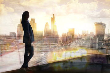 Young woman looking at the City of London at sunset. Planning the future, life and joy concept.