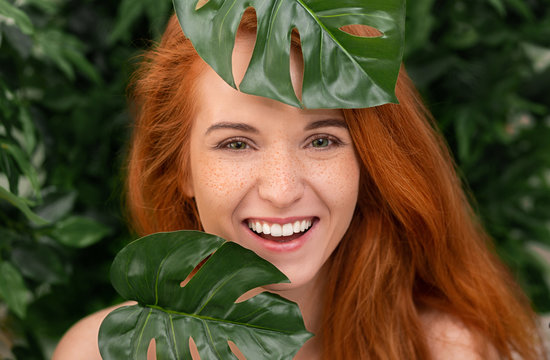 Cheerful redhead woman laughing through monstera leaves