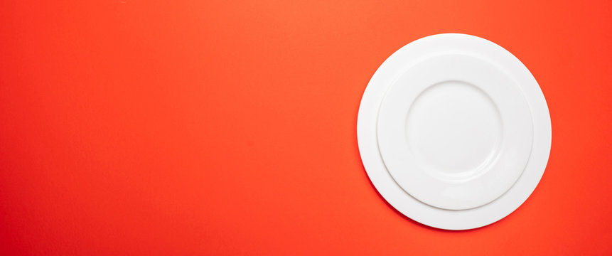 Empty white plates on red, orange color background, banner