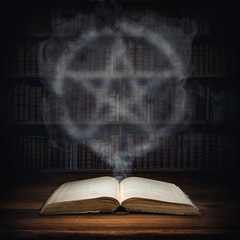 The old mysterious book and the smoke coming out of it is a sign of the pentagram. Occult, esoteric, divination, magic concept background.