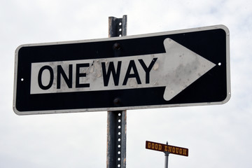 """Two signs, one saying """"good enough"""", the other """"one way"""""""