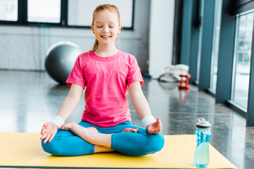 Ginger kid practicing yoga and sitting in lotus pose with closed eyes