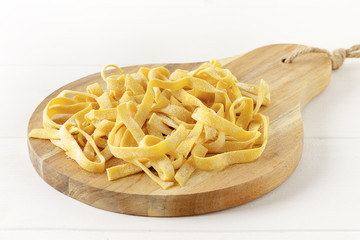 Homemade tagliatelle on chopping board on wooden white background