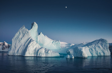 Obraz Close-up iceberg next to the Antarctica shoreline. The huge ice covered mountain with the basin. The glacier floating among the frozen polar ocean water. Breathtaking North pole landscape. - fototapety do salonu