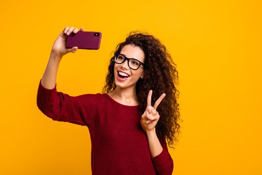 Portrait of her she nice cute attractive pretty cheerful wavy-haired lady wearing eyeglasses eyewear holding in hands cell making selfie showing v-sign isolated on bright vivid shine orange background