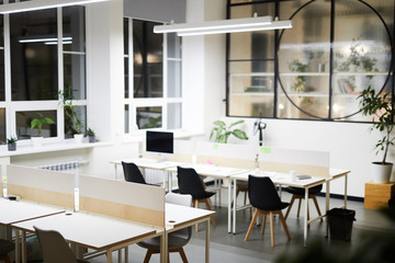 Modern open space office interior: black chairs at tables in rows under hanging lamp, potted plants near wall and on window sill