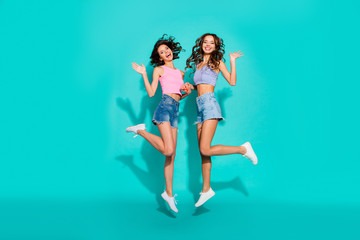 Full length body size photo jumping beautiful two wavy she her ladies hands arms raised say hi friendly wearing shiny jeans denim shorts tank tops isolated teal bright vivid background