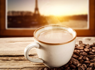 Hot coffee on window sill and Paris landscape